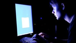 stock-footage-young-man-in-front-of-computer-screen-dark-night-room